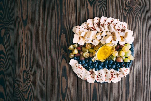 Asortyment serów i owoców na drewnianym stole. widok z góry.