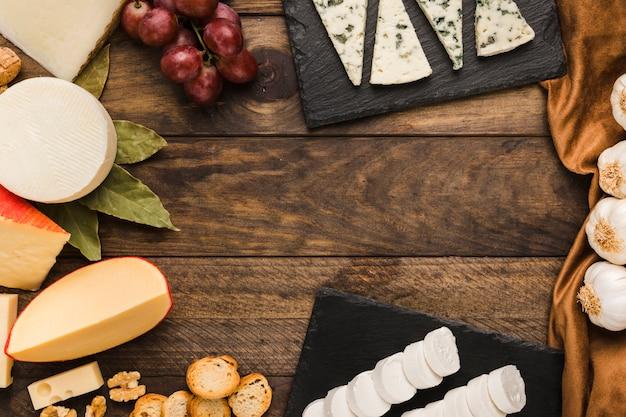 Asortyment serów; winogrona; kromka chleba; orzech na ciemnym drewnianym stole