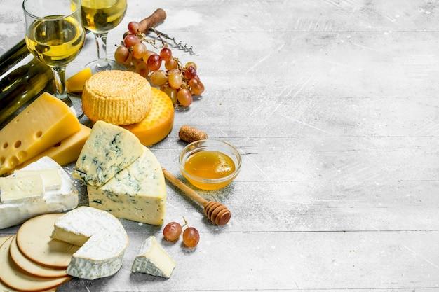 Asortyment serów z białym winem i miodem na rustykalnym stole.