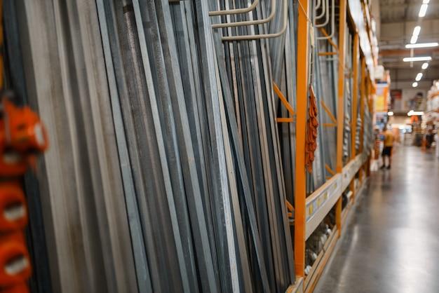 Asortyment sklepu na półce, nikt. wybór materiałów budowlanych w sklepie dla majsterkowiczów, rzędy produktów na stojakach