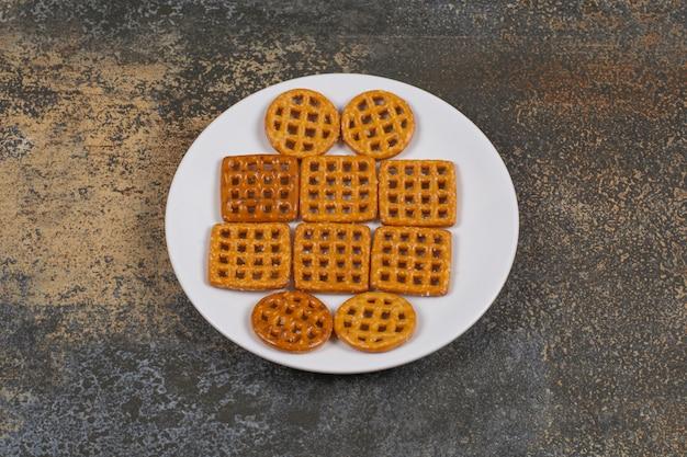 Asortyment solonych krakersów na białym talerzu.