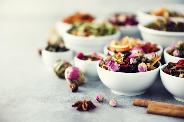 Asortyment suchej herbaty w białych miseczkach.