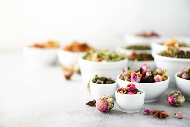Asortyment suchej herbaty w miseczkach.