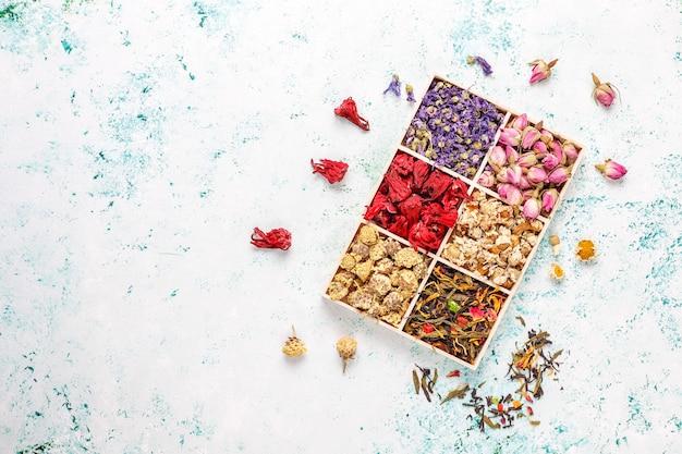 Asortyment suchej herbaty w złotych zabytkowych mini talerzach. rodzaje herbat w tle
