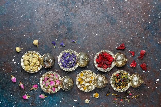 Asortyment suchej herbaty w złotych zabytkowych mini talerzach. rodzaje herbaty