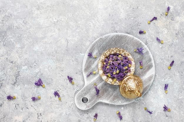 Asortyment suchej herbaty w złotych zabytkowych mini talerzach. tło rodzajów herbaty: hibiskus, rumianek, mieszana czarna herbata, suche róże, herbata z groszku motyla