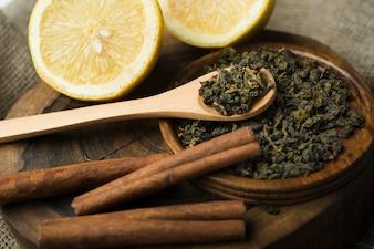 Asortyment suchej herbaty zioła z połówkami cytryny na drewnianej tacy
