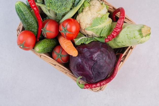 Asortyment surowych warzyw w drewnianym koszu.