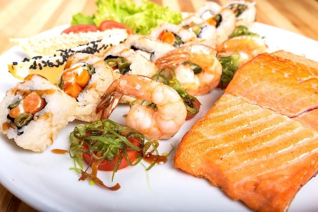 Asortyment sushi, krewetki i kawałek grillowanego łososia. w dowolnym celu.