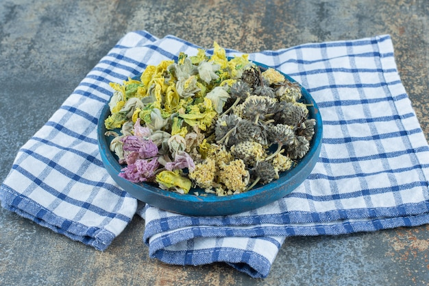 Asortyment suszonych kwiatów organicznych na niebieskim talerzu.