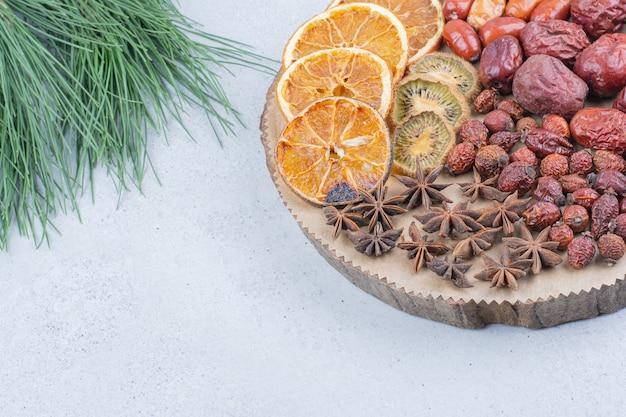 Asortyment suszonych owoców i goździków na drewnianym kawałku.