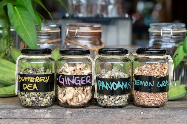 Asortyment suszonych przypraw w szklanych butelkach na drewnianym tle. suchy imbir, pandan, trawa cytrynowa i groszek motylkowy w szklanych słoikach, z bliska