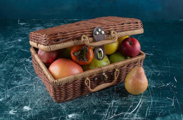 Asortyment świeżych owoców w drewnianej torbie.