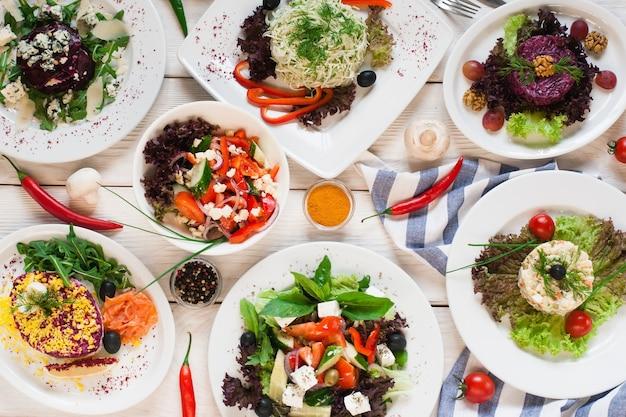 Asortyment świeżych sałatek warzywnych układany na płasko. widok z góry na wegetariański bufet ze smacznym dodatkiem