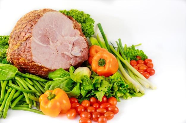 Asortyment świeżych warzyw i całej szynki wieprzowej. posiłek wielkanocny.