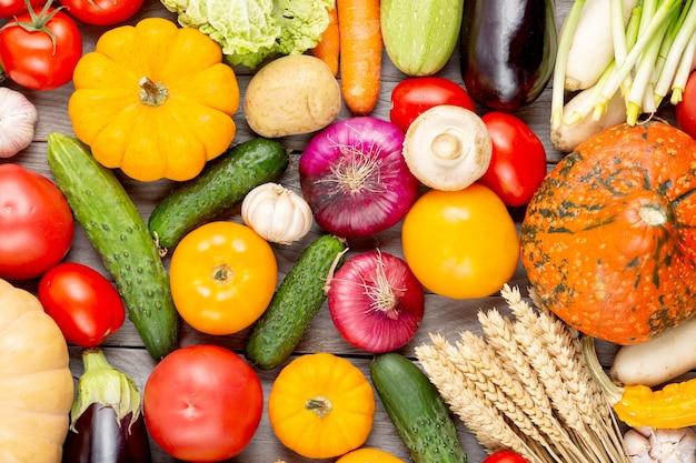 Asortyment świeżych warzyw jako tło. sezonowe bliska stół rolnika z warzywami. dynie, pomidory, kapusta, marchew, cebula, ogórek, melon, bakłażan, ziemniaki i inne.