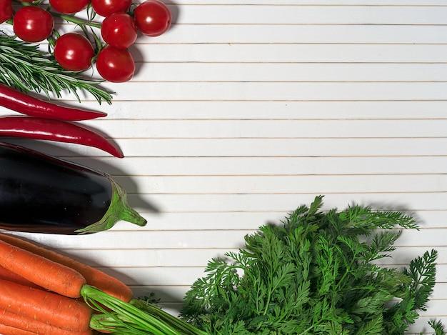 Asortyment świeżych warzyw. marchwianego czosnku pomidorów cebulkowej oberżyny gorący pieprz na białym drewnianym stołowym tle, odgórny widok