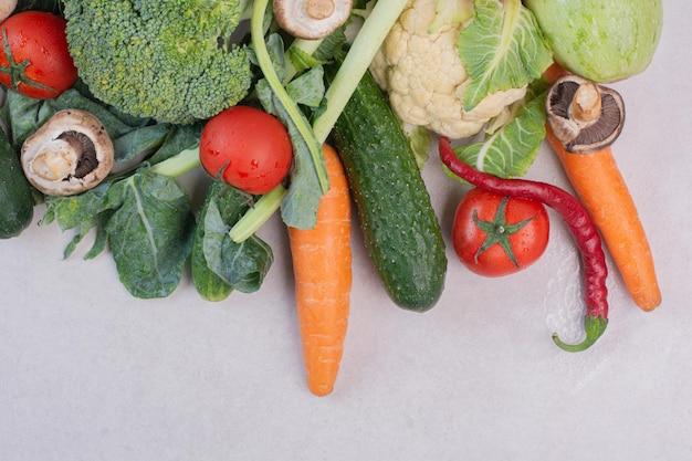Asortyment świeżych warzyw na białym stole.