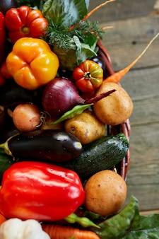 Asortyment świeżych warzyw w koszu, bio zdrowej, ekologicznej żywności na drewniane tła, styl rynku wiejskiego, produkty ogrodowe, dieta wegetariańska, czyste jedzenie.