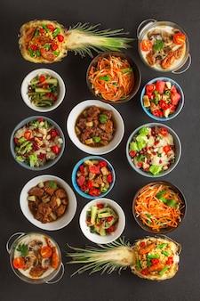 Asortyment tajskich potraw gotowanych w miski na czarnym tle betonu