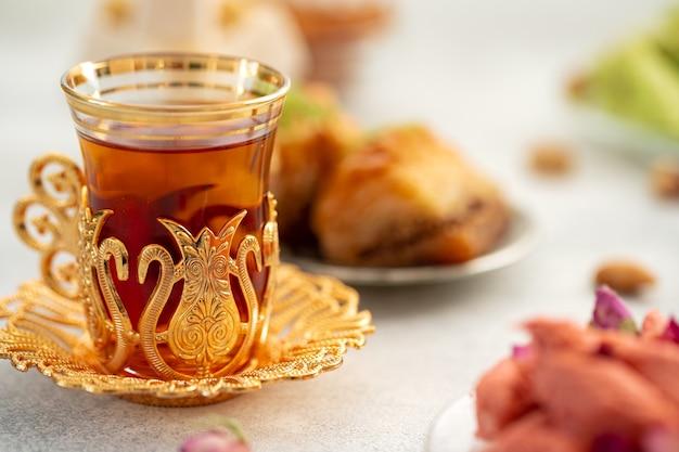 Asortyment tureckich przysmaków ze szklanką herbaty na szarym tle