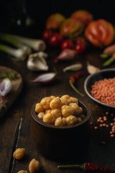 Asortyment warzyw, soczewica, ciecierzyca na brązowy drewniany stół, widok z góry