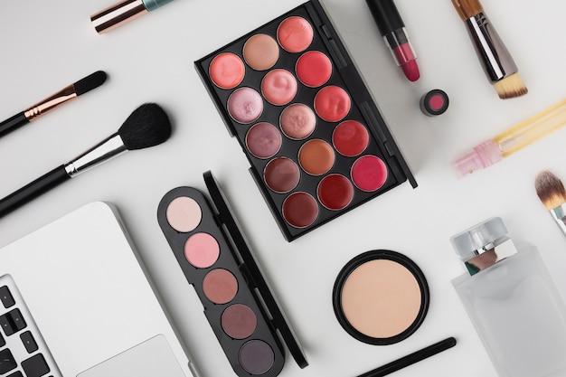 Asortyment widok z góry z paletami do makijażu i laptopem