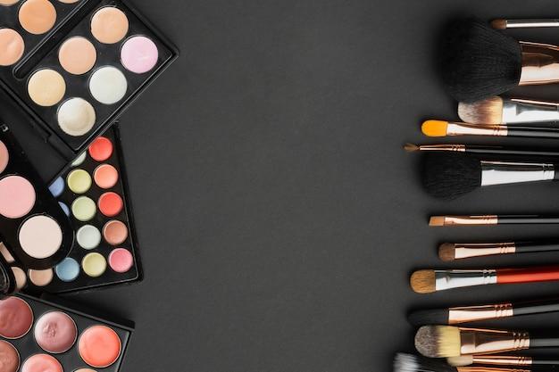 Asortyment widoków z góry z pędzlami do makijażu i paletami
