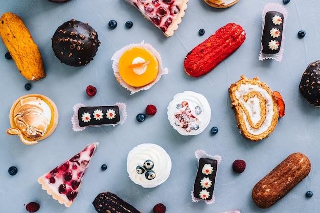 Asortyment wyrobów cukierniczych, różne rodzaje ciast i deserów na stole.