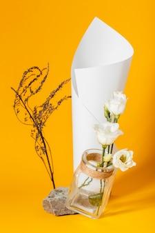 Asortyment z białymi różami w wazonie z papierowym rożkiem