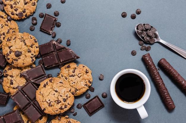 Asortyment z ciastkami, pałeczkami czekoladowymi i kawą