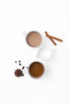 Asortyment z filiżankami kawy i paluszkami cynamonu