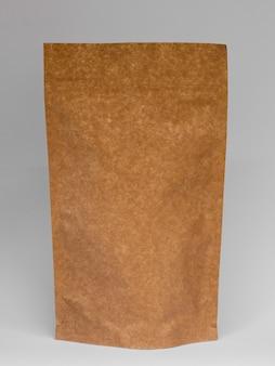 Asortyment z papierową torbą i szarym tłem