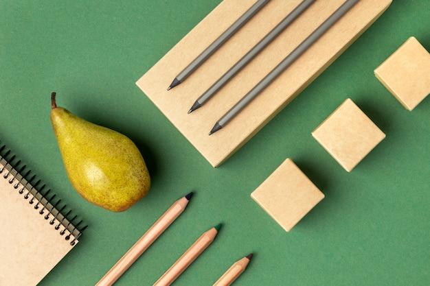 Asortyment z widokiem z góry z elementami papeterii i owocami