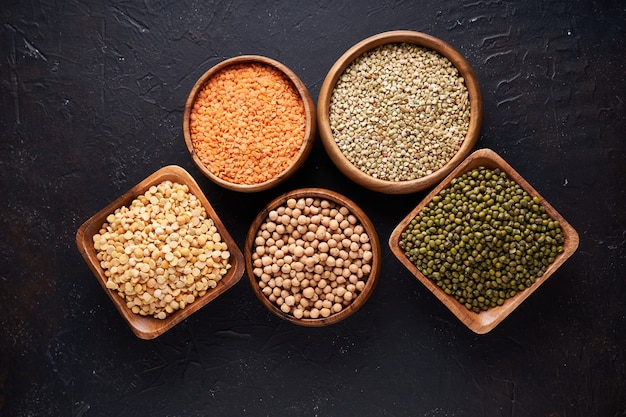 Asortyment zbóż, roślin strączkowych, zbóż, ziaren, soczewicy, ciecierzycy, groszku, fasoli, płatków owsianych w drewnianych misach