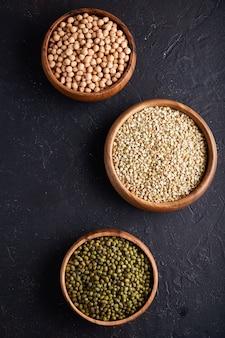 Asortyment zbóż, roślin strączkowych, zbóż, ziaren, soczewicy, ciecierzycy, groszku, fasoli w drewnianych misach