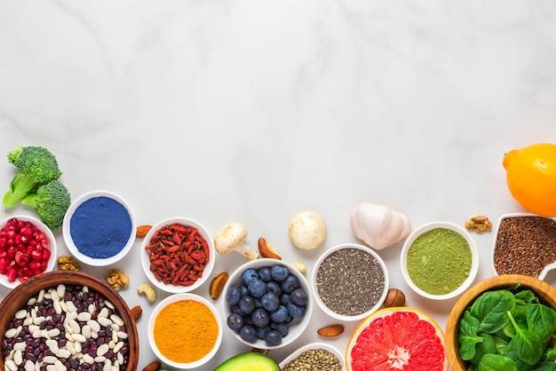 Asortyment zdrowej żywności wegańskiej na tle marmuru. warzywa, matcha, acai, kurkuma, owoce, jagody, awokado, grzyby, orzechy i nasiona superfoods. widok z góry