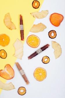 Asprtied suszone owoce, chipsy rozrzucone na białym i żółtym tle. chipsy owocowe. koncepcja zdrowego odżywiania, przekąska, bez cukru. widok z góry, kopia przestrzeń.