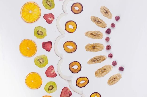 Asprtied suszone owoce, żetony rozrzucone na białym tle. chipsy owocowe. koncepcja zdrowego odżywiania, przekąska, bez cukru. widok z góry, kopia przestrzeń.