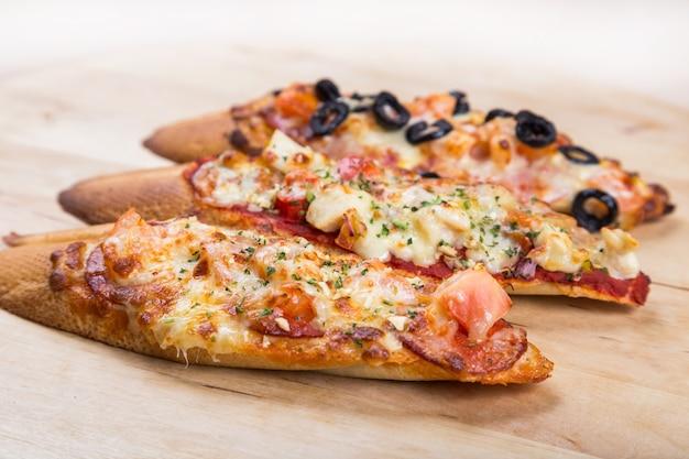 Assorti bruschetta z kiełbasą, serem, pomidoru fron dużą białą baguette na drewnianym tle