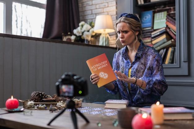Astrologia i pieniądze. przyjemna młoda kobieta opowiadająca o ciekawej książce podczas nagrywania wideo na swoim blogu