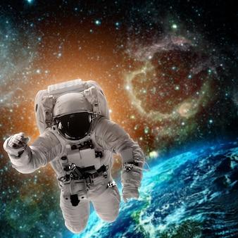 Astronauta leci nad ziemią w kosmosie. elementy tego obrazu dostarczone przez nasa