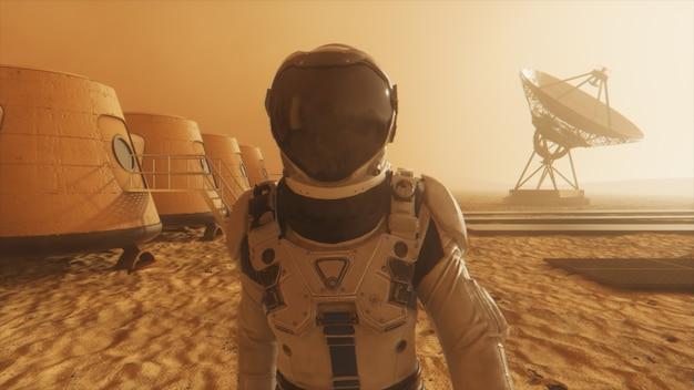Astronauta na planecie mars, okrążający swoją bazę. astronauta idący wzdłuż bazy.