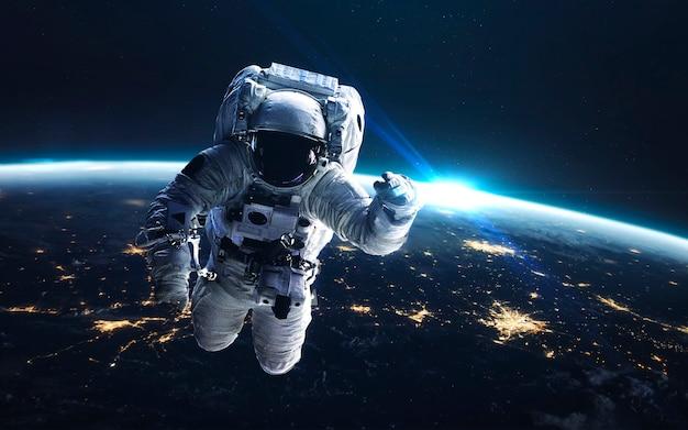 Astronauta na spacerze kosmicznym. ziemia nocą, światła miasta z orbity. elementy tego zdjęcia dostarczone przez nasa
