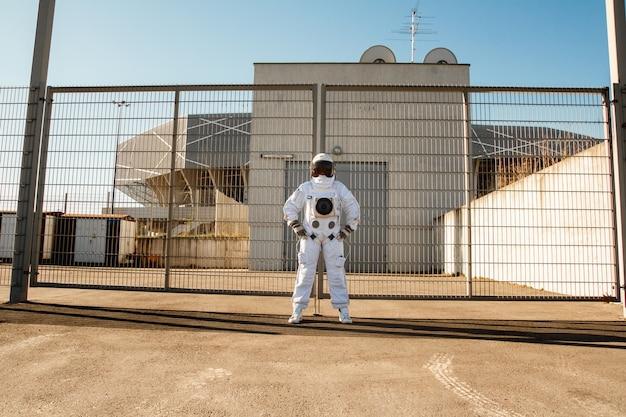 Astronauta na tle futurystycznego miasta, spojrzenie na przyszłość. fantastyczny kostium kosmiczny.