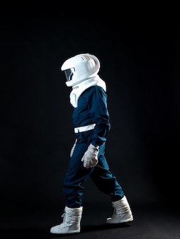 Astronauta porusza się w warunkach niskiej grawitacji. bohater opowieści science fiction jest pionierem eksploracji kosmosu. młody mężczyzna w skafandrze kosmicznym