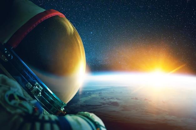 Astronauta w skafandrze kosmicznym z hełmem w kosmosie z niebieską planetą ziemią i promieniami zachodów słońca. kosmonauta w kosmosie, koncepcja