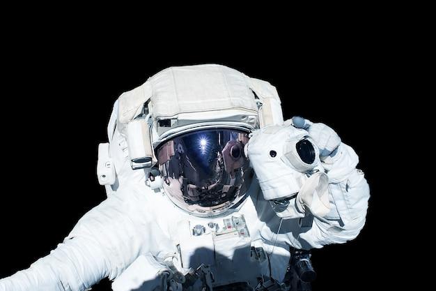 Astronauta w skafandrze na białym na czarnym tle. elementy tego obrazu dostarczyła nasa. zdjęcie wysokiej jakości
