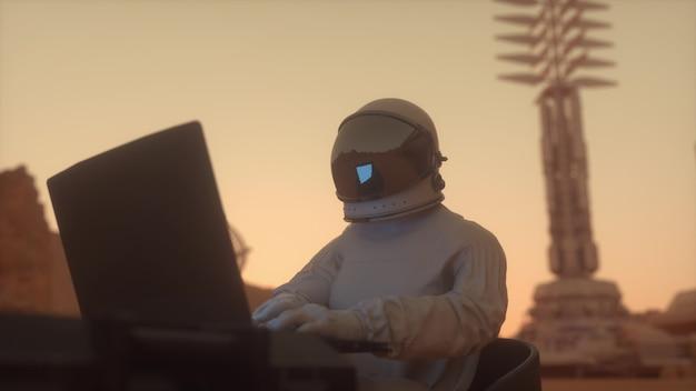 Astronauta w skafandrze pracuje na laptopie w kosmicznej koloni na jednej z planet