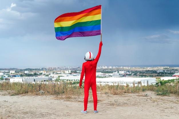 Astronauta z flagą lgbt. widok z tyłu